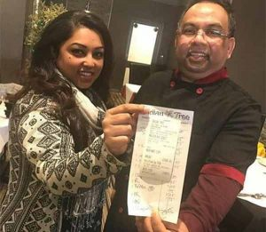 Restaurant director Luna Ekuch and chef Babu display the bill with a tip of £1,000 left by a loyal customer last week.