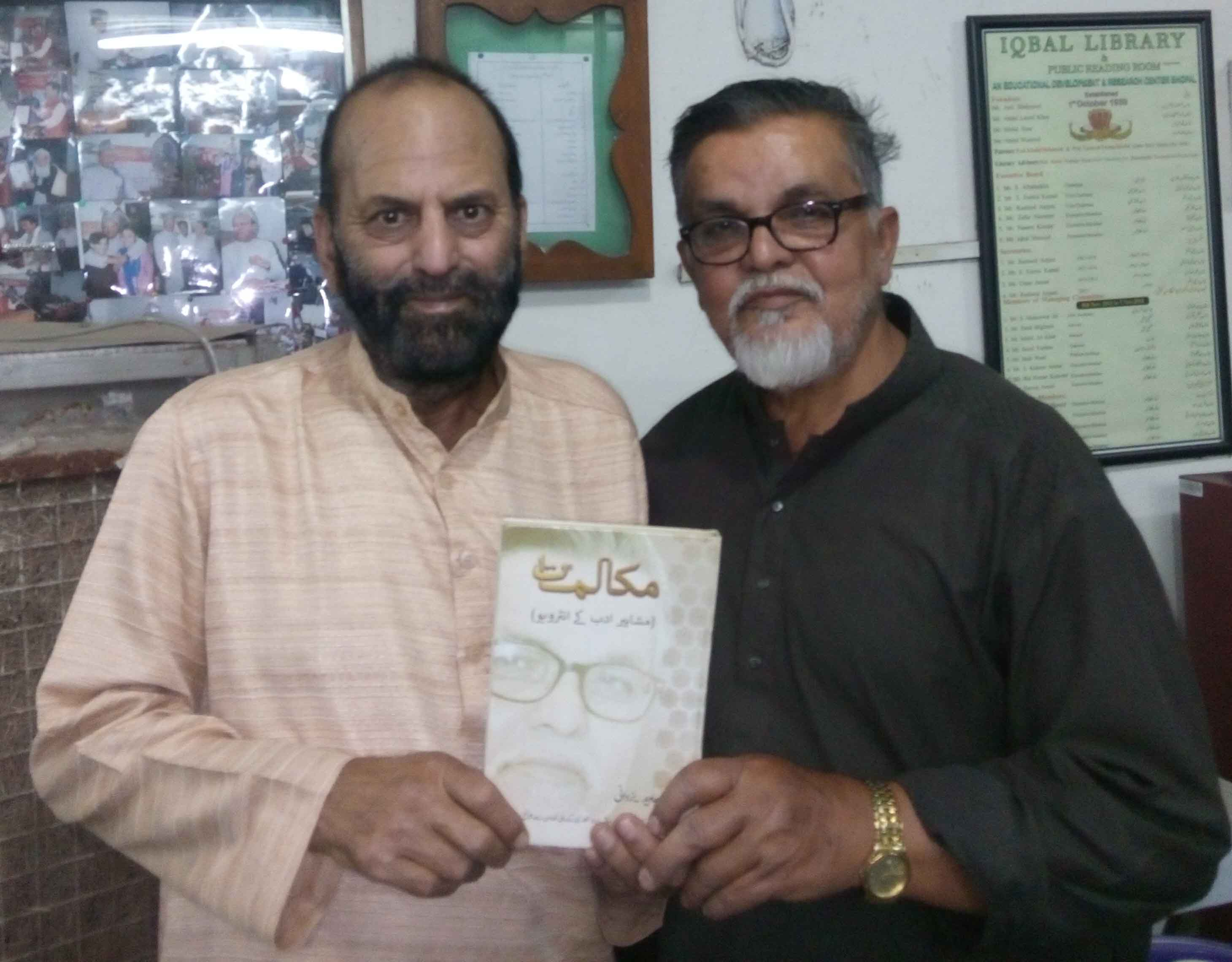 Javed Yadani (right) presenting his latest book to Muslim Saleem on March 31, 2017